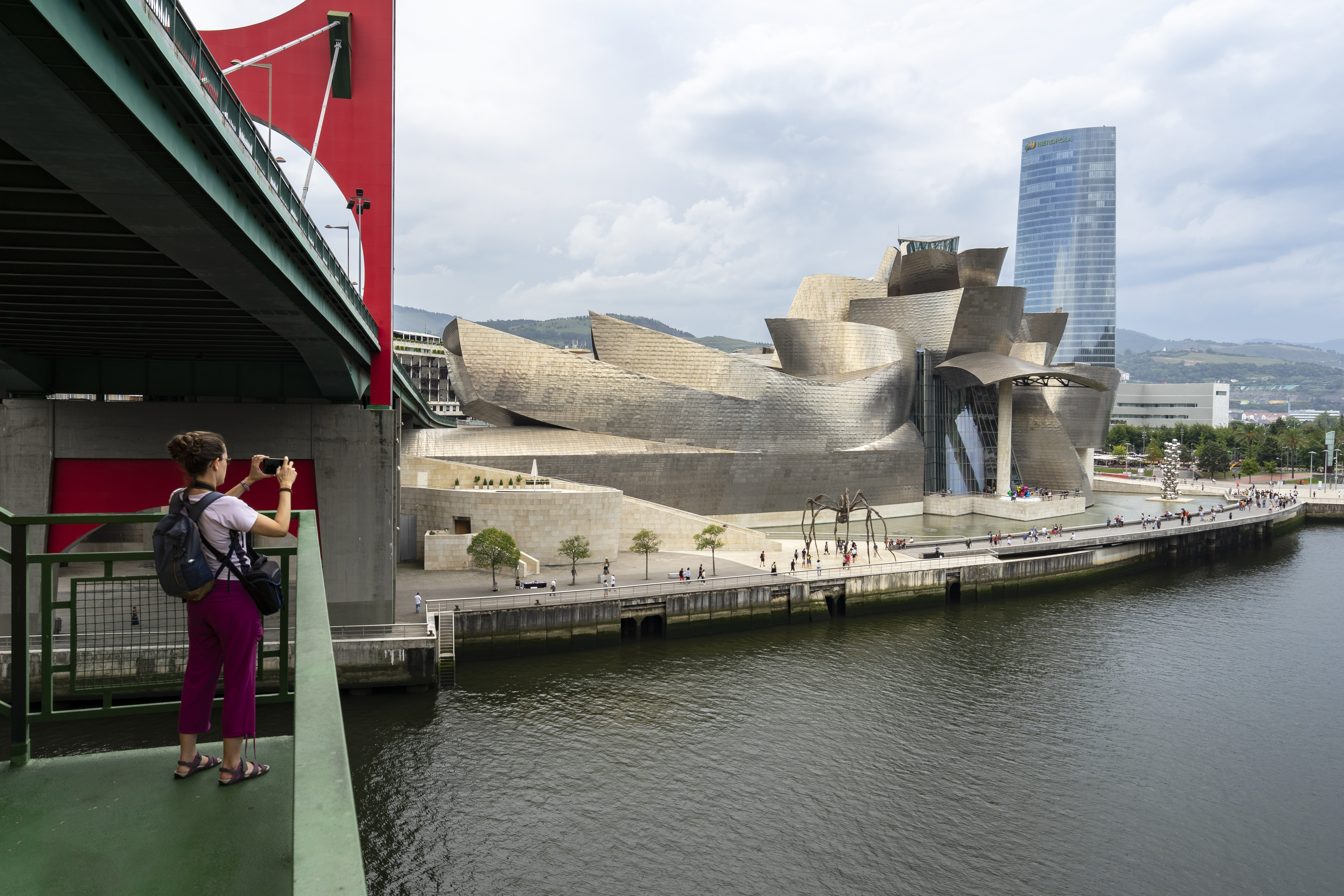 Tourist taking photos with mobile of Guggenheim museum. Travel photography. Photography concept.