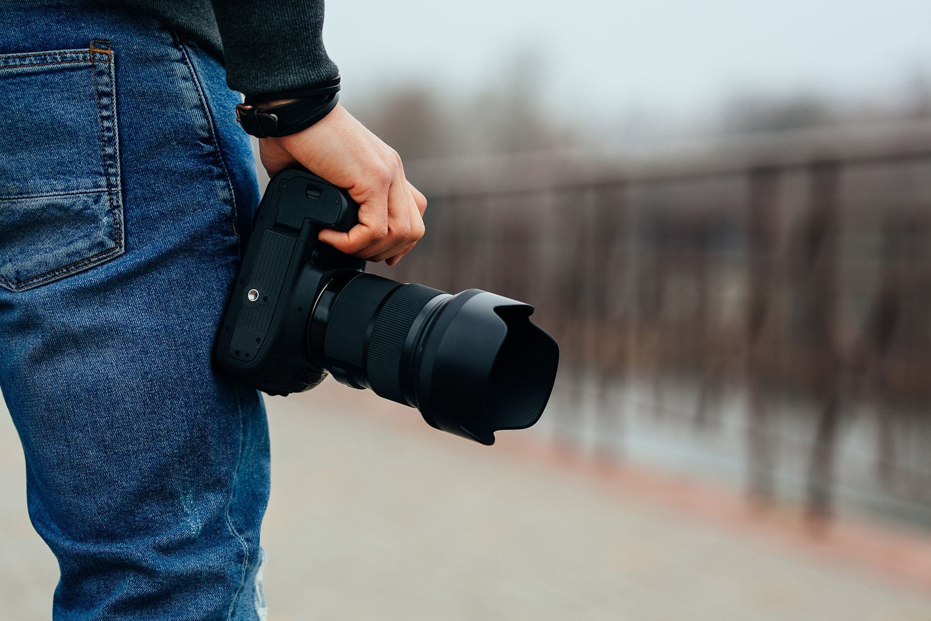 Male hands holding professional camera outdoors
